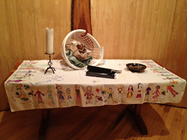 altar setup for summer 2013 - a laundry basket, some file folders, and a candle